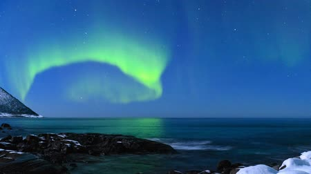 norvégia : HD Time-lapse of Northern Light Aurora Borealis in the night sky over Senja island in Northern Norway. Snow covered mountains in the background where moonlight is illuminating landscape.