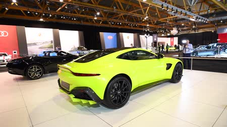tourer : Aston Martin Vantage in bright green and DB11 Convertible exclusive Grand Tourer sports cars on display at the 2018 European motor show in Brussels.