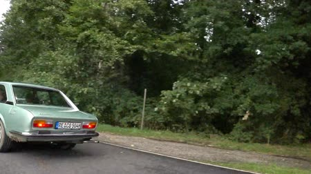 двухместная карета : Peugeot 504 Coupe classic car driving on a country road. The car is doing a demonstration drive during the 2017 Classic Days. Стоковые видеозаписи