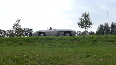 lightweight : Mercedes-Benz 300 SLS Roadster classic lightweight racing car driving on a country road. The car is doing a demonstration drive during the 2017 Classic Days event at Schloss Dyck. Stock Footage