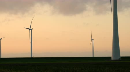 dioksit : Wind turbines with turning blades in the wind in an offshore windpark during sunset.