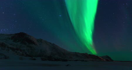 к северу : Northern Lights, polar light or Aurora Borealis in the night sky over the Lofoten islands in Northern Norway time lapse.