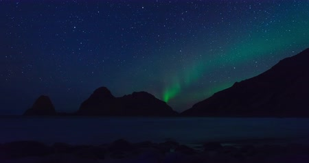 norueguês : Northern Lights, polar light or Aurora Borealis in the night sky over Vesteralen islands in Northern Norway time lapse.