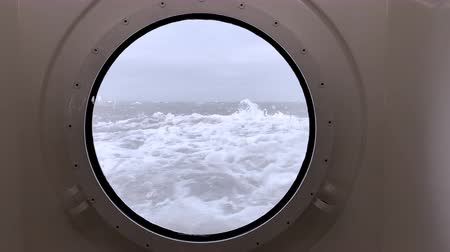 válečné loďstvo : View through a porthole on a stormy sea with waves hitting the ship at the Wadden Sea between Lauwersoog and Schiermmonnikoog Dostupné videozáznamy