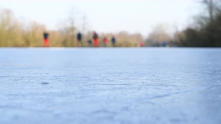 waterways : People ice skating on a frozen lake next to the river IJssel in Holland during a beautiful winter day winter. People are enjoying this typical Dutch winter activity. Stock Footage