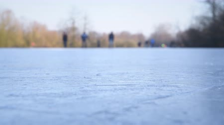 водный путь : People ice skating on a frozen lake next to the river IJssel in Holland during a beautiful winter day winter. People are enjoying this typical Dutch winter activity. Стоковые видеозаписи