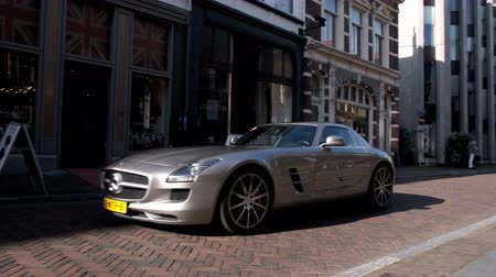 status : Mercedes-AMG SLS sports car driving in a street in the city of Zwolle during a sunny summer morning. People in the background are looking at the cars. Stock Footage