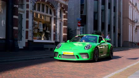modo : Porsche 911 GT3 (991) sports car driving in a street in the city of Zwolle during a sunny summer morning. People in the background are looking at the cars.