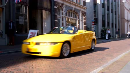 alfa : Alfa Romeo RZ Roadster Zagato convertible sports car driving in a street in the city of Zwolle during a sunny summer morning. People in the background are looking at the cars. Stock Footage