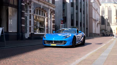 durum : Ferrari 812 Superfast sports car driving in a street in the city of Zwolle during a sunny summer morning. People in the background are looking at the cars.
