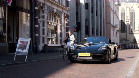 modo : Porsche 718 Boxster sports car driving in a street in the city of Zwolle during a sunny summer morning. People in the background are looking at the cars. Stock Footage