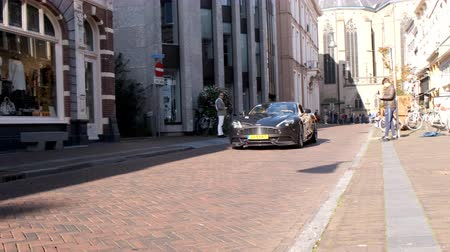 série : Aston Martin Vanquish sports car driving in a street in the city of Zwolle during a sunny summer morning. People in the background are looking at the cars.