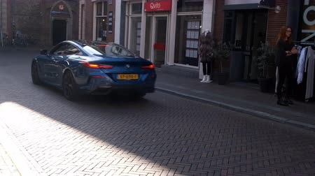 modo : BMW 8 Series Coupe BMW M850i exclusive sports car driving in a street in the city of Zwolle during a sunny summer morning. People in the background are looking at the cars.