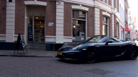 паук : Porsche Boxster GTSsports car driving in a street in the city of Zwolle during a sunny summer morning. People in the background are looking at the cars. Стоковые видеозаписи