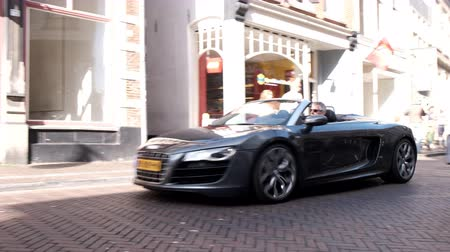 roadster : Audi R8 Spyder sports car driving in a street in the city of Zwolle during a sunny summer morning. People in the background are looking at the cars. Stock Footage