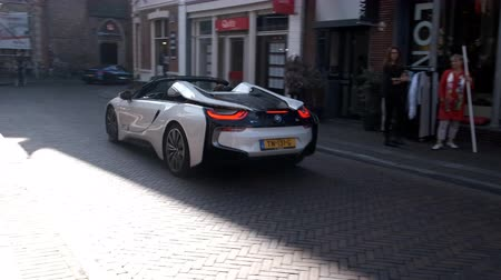 roadster : BMW i8 Roadster exclusive hybrid sports car driving in a street in the city of Zwolle during a sunny summer morning. People in the background are looking at the cars.