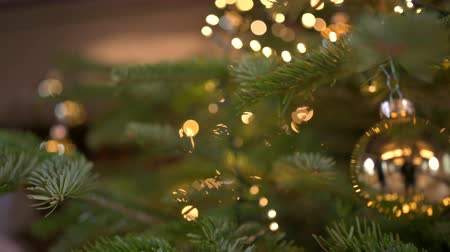 esparso : Christmas Fir Tree decorated with christmas balls and defocused lights in the background. Handheld shot with limited depth of field. Stock Footage