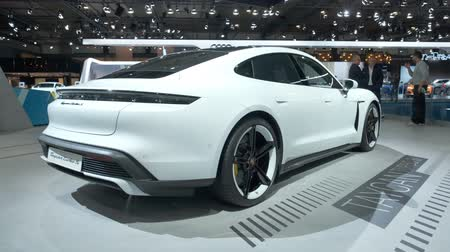 melez : BRUSSELS, BELGIUM - JANUARY 9: Porsche Taycan Turbo S all-electric luxury performance car on display at Brussels Expo. Handheld gimbal shot around the car. Stok Video