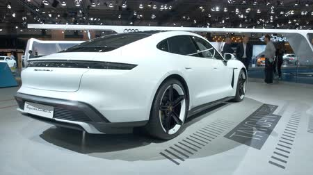 berlina : BRUSSELS, BELGIUM - JANUARY 9: Porsche Taycan Turbo S all-electric luxury performance car on display at Brussels Expo. Handheld gimbal shot.