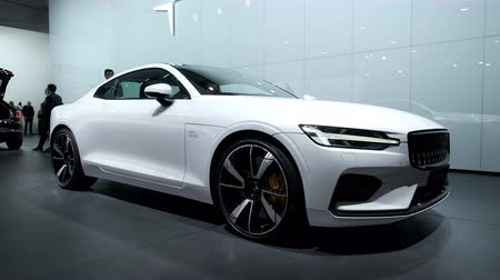 двухместная карета : BRUSSELS, BELGIUM - JANUARY 8, 2020: Polestar 1 hybrid sports car coupe in white on display at Brussels Expo. Polestar is the performance company and brand of Volvo Cars. Handheld gimbal shot around the car.