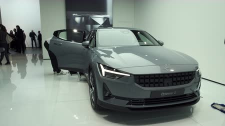melez : BRUSSELS, BELGIUM - JANUARY 9, 2020: Polestar 2 all-electric 5-door fastback car in grey on display at Brussels Expo. Handheld gimbal shot around the car.