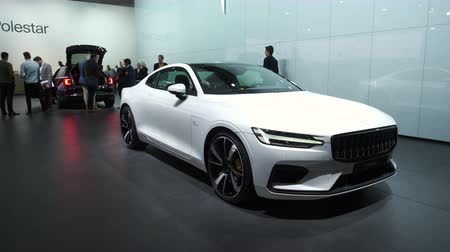 двухместная карета : BRUSSELS, BELGIUM - JANUARY 8, 2020: Polestar 1 hybrid sports car coupe in white on display at Brussels Expo. Polestar is the performance company and brand of Volvo Cars. Handheld gimbal shot. Стоковые видеозаписи