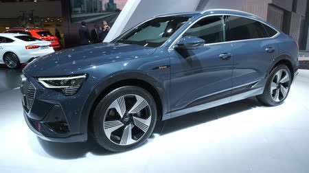двухместная карета : BRUSSELS, BELGIUM - JANUARY 9, 2020: Audi e-tron Sportback full electric luxury crossover SUV car on display at Brussels Expo. Handheld gimbal shot.