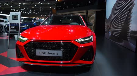 durum : BRUSSELS, BELGIUM - JANUARY 8, 2020: Audi RS6 Avant performance station wagon in bright red on display at Brussels Expo. Handheld gimbal shot. Stok Video