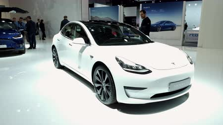 stationary : BRUSSELS, BELGIUM - JANUARY 9, 2020: Tesla Model 3 electric compact sedan car interior in white on display at Brussels Expo Stock Footage
