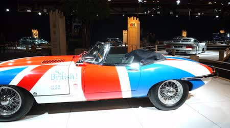 tipo : BRUSSELS, BELGIUM - JANUARY 8 ,2020: Jaguar E-Type Roadster classic sports car with a Uninon Jack flag painted on the body on display at Brussels Expo Vídeos