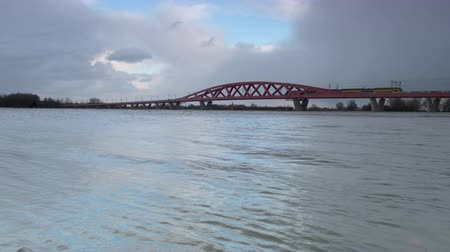 Water running over the floodplains of the river IJssel at the Hanzeboog train bridge during flooding caused by high water levels in the river in Overijssel The Netherlands Стоковые видеозаписи
