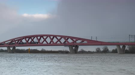 Water running over the floodplains of the river IJssel at the Hanzeboog train bridge during flooding caused by high water levels in the river in Overijssel The Netherlands. A train is passing over the bridge in the distance.