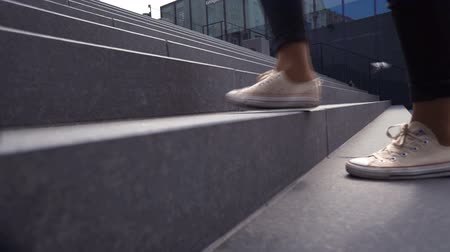 step : Girl walking on stairs. Female legs on the road