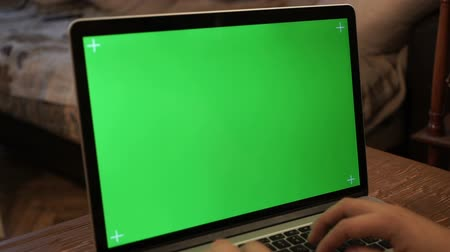 komputer stacjonarny : Male hands typing on a green screen laptop.