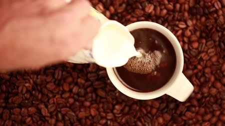núpcias : This is an overhead video that was shot with the Canon 5d Mark III of a cup of black coffee being poured that is surrounded by fresh coffee beans. Cream and sugar are then added and then everything is stirred at the end. Stock Footage