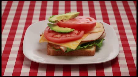 sanduíche : This is a step by step video of a turkey sandwich being built on a red and white checkered picnic table cloth.It has a lot of fresh healthy ingredients such as tomatoes, pickles, lettuce, avocado and cheese.It has a lot of fresh healthy ingredients such a