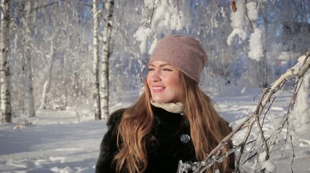 зима : A beautiful woman is happy and walks in the park on a winter day Стоковые видеозаписи
