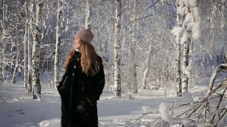 couro : A beautiful woman is happy and walks in the park on a winter day Vídeos