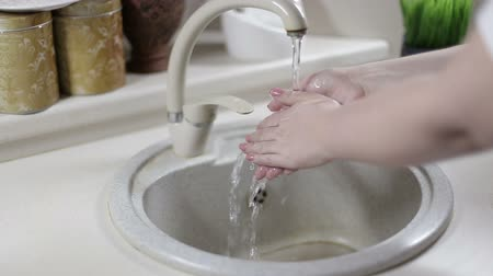 mycie rąk : A closeup shot of a woman hand washing in the sink . Girl cleaning her hand .
