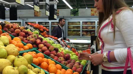 идущий : Antalya, Turkey - 25 March 2016: Mother and douther approaching the fruits shelf, choosing some apple and putting them in packet in supermarket.