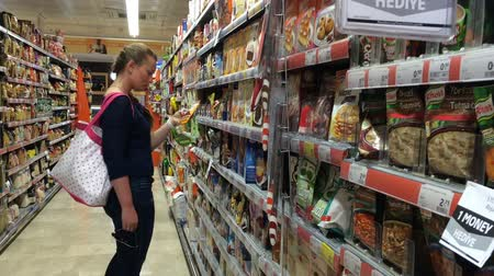 um : Young woman with bag chooses food in supermarket. Woman Choosing Products in Supermarket. Stock Footage