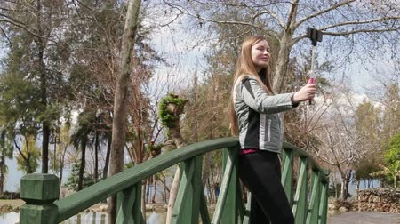 stay active : Young happy woman taking self portrait standing on the wooden bridge using smartphone mobile cell phone camera. Stock Footage