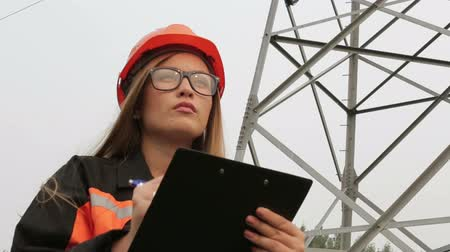 requiring : Woman engineer working near an electrical substation lines, power lines, teamwork.