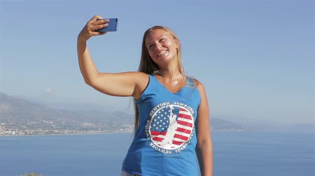 The American traveler photographed themselves on the background of ocean use your smartphone while standing on the mountain