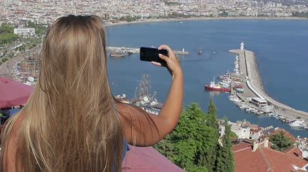 The American traveler makes a photo of the ocean use your smartphone while standing on the mountain