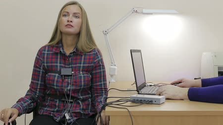 Lie-detector test, a woman answers the questions of the expert
