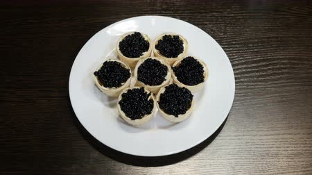 икра : On the table is a plate of canapes of black caviar