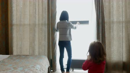 unveil : Young woman unveil curtain and looking out of window and a child runs up to her. Hotel