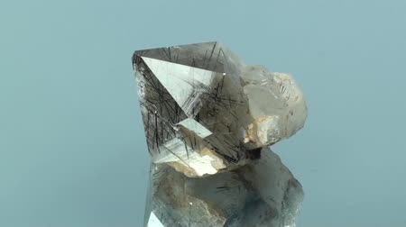 semi precious : Black Rutile Quartz crystal, close-up, seamlessly rotating on glass surface, locality, Pakistan.