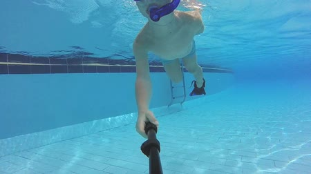 Small boy with mask and snorkel swimming in pool